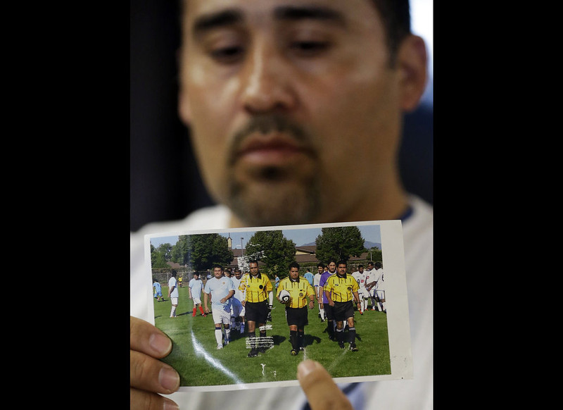. Jose Lopez points to an undated photo of Ricardo Portillo, center, his brother-in-law, following a news conference, at Intermountain Medical Center, in Murray, Utah on May 2, 2013. Portillo, a 46-year-old soccer referee, slipped into a coma and died Saturday night, May 4, 2013, after he was punched by a teenage player during a game police said. (AP Photo/Rick Bowmer, File)