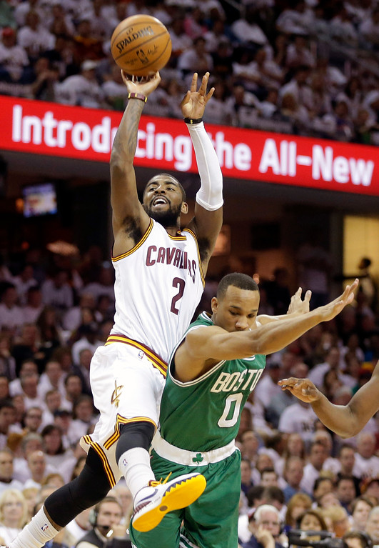 . Cleveland Cavaliers\' Kyrie Irving (2) is fouled by Boston Celtics\' Avery Bradley (0) while shooting in the fourth quarter of a first-round NBA playoff basketball game Sunday, April 19, 2015, in Cleveland. Irving made the basket and the free throw on his way to a 30-point afternoon in the Cavaliers\' 113-100 win. (AP Photo/Mark Duncan)