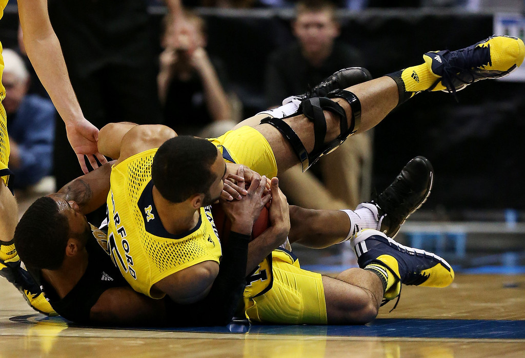 . Karl Cochran #2 of the Wofford Terriers and Jordan Morgan #52 of the Michigan Wolverines vie for the ball in the first half during the second round of the 2014 NCAA Men\'s Basketball Tournament at BMO Harris Bradley Center on March 20, 2014 in Milwaukee, Wisconsin.  (Photo by Jonathan Daniel/Getty Images)