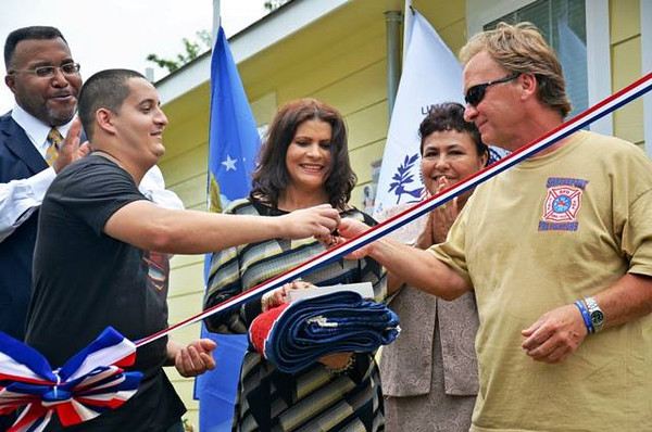 Veteran homeowner partner Miguel Guigni receives the keys to his home.