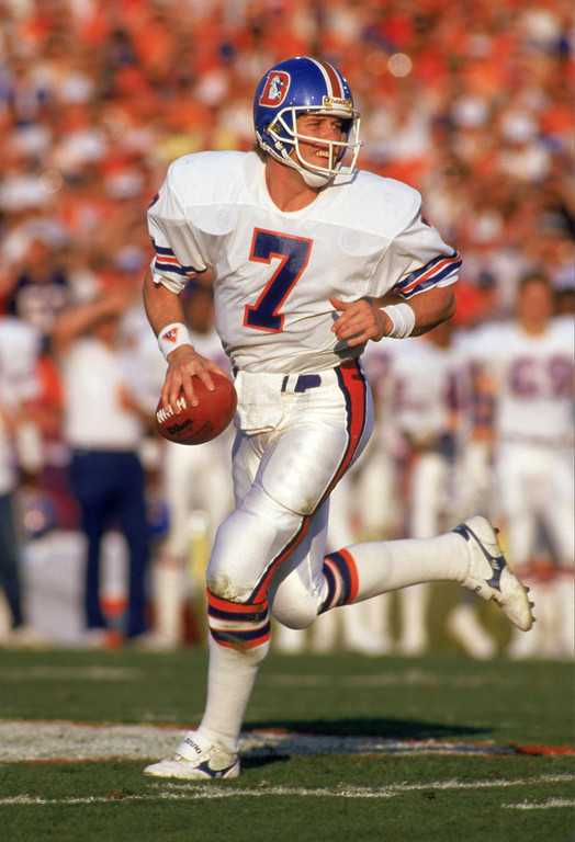 . Quarterback John Elway #7 of the Denver Broncos runs with the ball as he looks down field for a receiver during Super Bowl XXI against the New York Giants at the Rose Bowl on January 25, 1987 in Pasadena, California.   (Photo by George Rose/Getty Images)