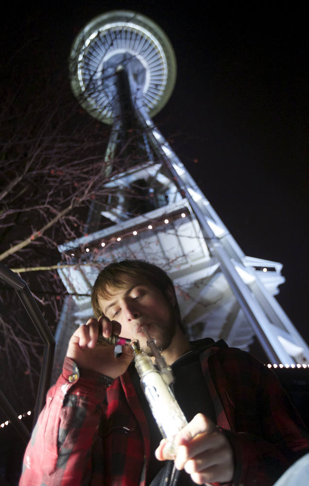 . Paul of Tacoma, who declined to give his last name smokes marijuana from a water pipe underneath the Space Needle shortly after a law legalizing the recreational use of  marijuana took effect on December 6, 2012 in Seattle, Washington.  Voters approved an initiative to decriminalize the recreational use of marijuana making it one of the first states to do so. (Photo by Stephen Brashear/Getty Images)