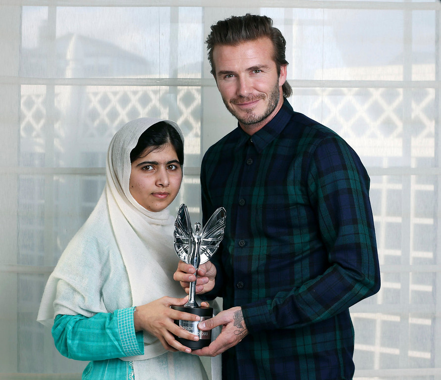 . David Beckham, right,  presents a Mirror Pride of Britain Teenager of Courage Award to Malala Yousafzai, a Pakistani schoolgirl who was shot by the Taliban for going to school.  (AP Photo/Philip Coburn, Daily Mirror via PA)