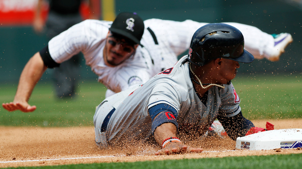 . Cleveland Indians\' Francisco Lindor, front, is tagged out at third base by Colorado Rockies third baseman Nolan Arenado on the back end of a double play hit into by Michael Brantley during the fourth inning of a baseball game Wednesday, June 7, 2017, in Denver. Colorado won 8-1. (AP Photo/David Zalubowski)