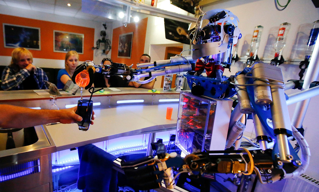 ". Humanoid robot bartender ""Carl\"" pours a spirit into the cocktail shaker of a bartender to prepare a drink for a guest at the Robots Bar and Lounge in the eastern German town of Ilmenau, July 26, 2013. \""Carl\"" - developed and built by mechatronics engineer Ben Schaefer who runs a company for humanoid robots - prepares spirits for the mixing of cocktails and is able to interact with customers in small conversations. Picture taken July 26, 2013. REUTERS/Fabrizio Bensch"