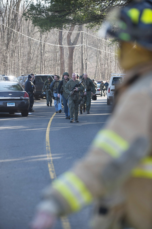 . NEWTOWN, CT - DECEMBER 14:  Connecticut State Police walk on Dickson Street  from the scene of an elementary school shooting on December 14, 2012 in Newtown, Connecticut. According to reports, there are about 27 dead, 18 children, after a gunman opened fire in at the Sandy Hook Elementary School. The shooter was also killed.  (Photo by Douglas Healey/Getty Images)