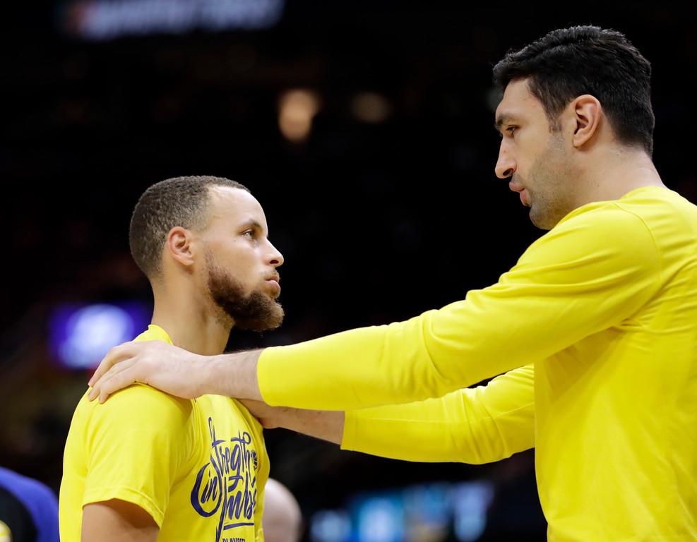 . Golden State Warriors center Zaza Pachulia, right, talks with Stephen Curry during halftime in Game 4 against the Cleveland Cavaliers in basketball\'s NBA Finals, Friday, June 8, 2018, in Cleveland. (AP Photo/Tony Dejak)