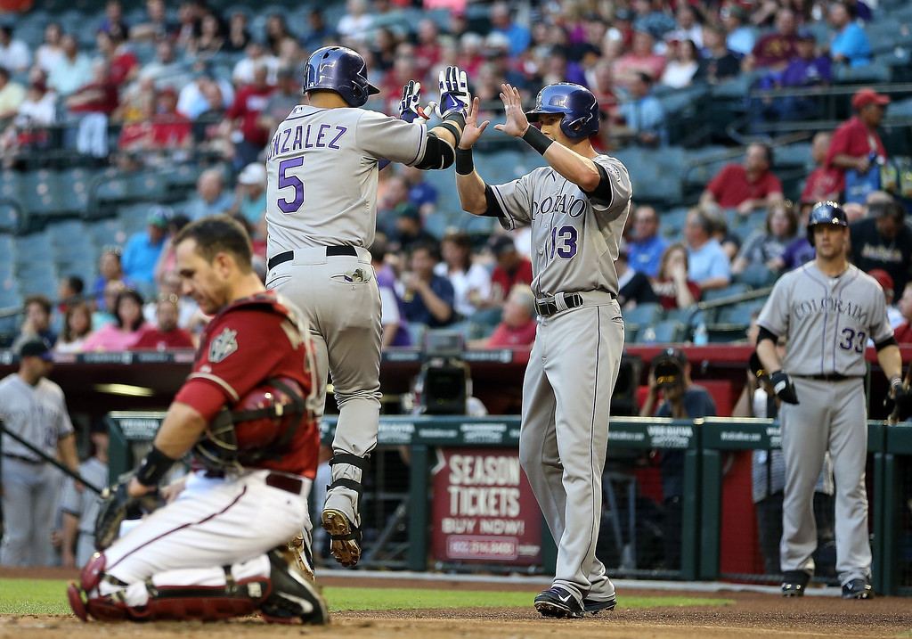 . Carlos Gonzalez #5 of the Colorado Rockies is congratulated by Drew Stubbs #13 after Gonzalez hit a two run home-run against the Arizona Diamondbacks during the first inning of the MLB game at Chase Field on April 30, 2014 in Phoenix, Arizona.  (Photo by Christian Petersen/Getty Images)