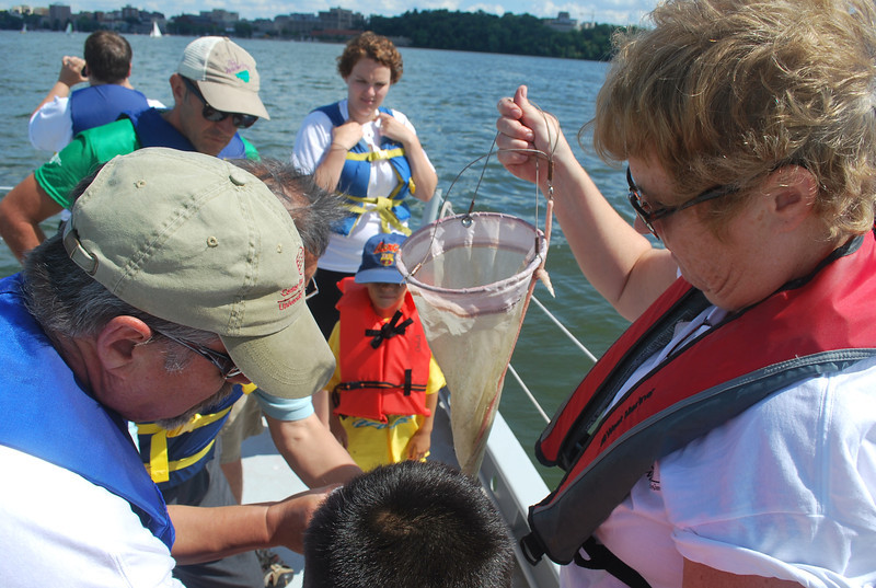 Mary Possin and Dave Harring help a young visitor collect tiny plants and animals caught in a plankton net.