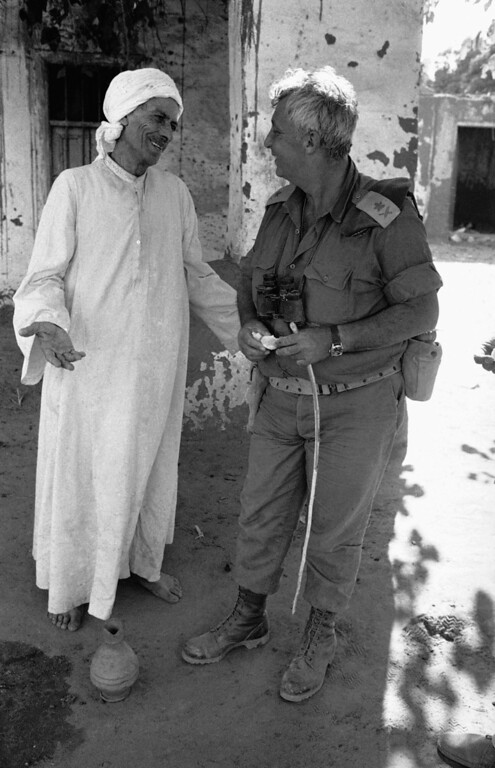 . In this Oct. 23, 1973 file photo, Israeli Major General Ariel Sharon, who commands Israeli units operating in the Egyptian west bank of the Suez canal, smiles with an Egyptian farmer in an unidentified village near Ismailia in Egypt.  (AP Photo/Horst Faas, File)
