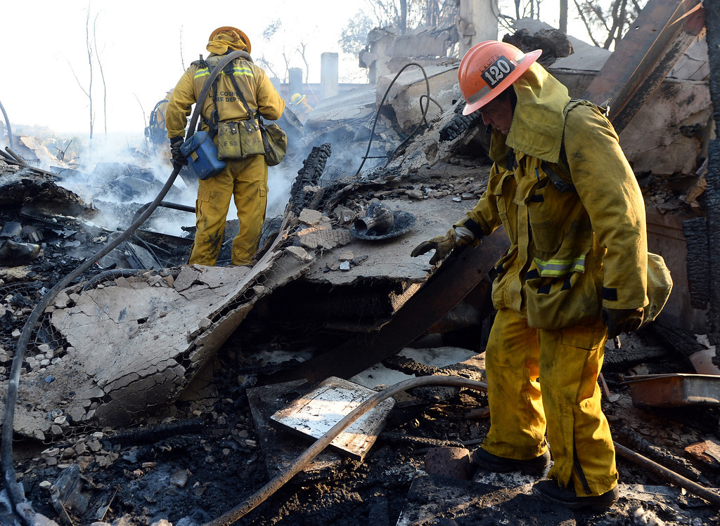 . A Los Angeles County firefighter out of San Dimas and a capt. out of Diamond Bar works on the fire at the Singer Estate a top Kregmont Dr. where a guest home and six car garage burned during the Colby Fire, a 1,700-acre plus brush fire that ignited in the Angeles National Forest north of Glendora  threatening homes and prompting mandatory evacuations in Glendora, Calif., on Thursday, Jan. 16, 2014. (Keith Birmingham Pasadena Star-News)