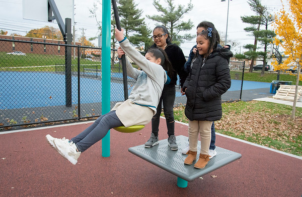 11/04/19 Wesley Bunnell | StaffrrA ribbon cutting was held at Chesley Park celebrating the completion of the Phase 2 renovation project. MIlexis Nieves grabs hold of a rope slide as friends Dehleila Rosario, Leilani Gonzalez, R, and Anna Maldonado, rear, smile and wait their turn.