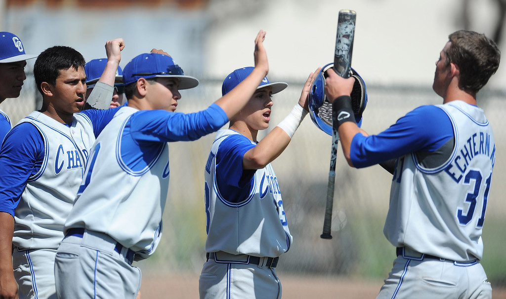 . Charter Oak\'s Kevin Ecternkamp (31) high fives teammates after scoring on a sac bunt by Nick Glick (not pictured) in the third inning of the Championship game of the Gladstone Baseball Tournament against Duarte at Gladstone High School on Wednesday, April 3, 2013 in Covina, Calif. Charter Oak won 5-3. (Keith Birmingham Pasadena Star-News)