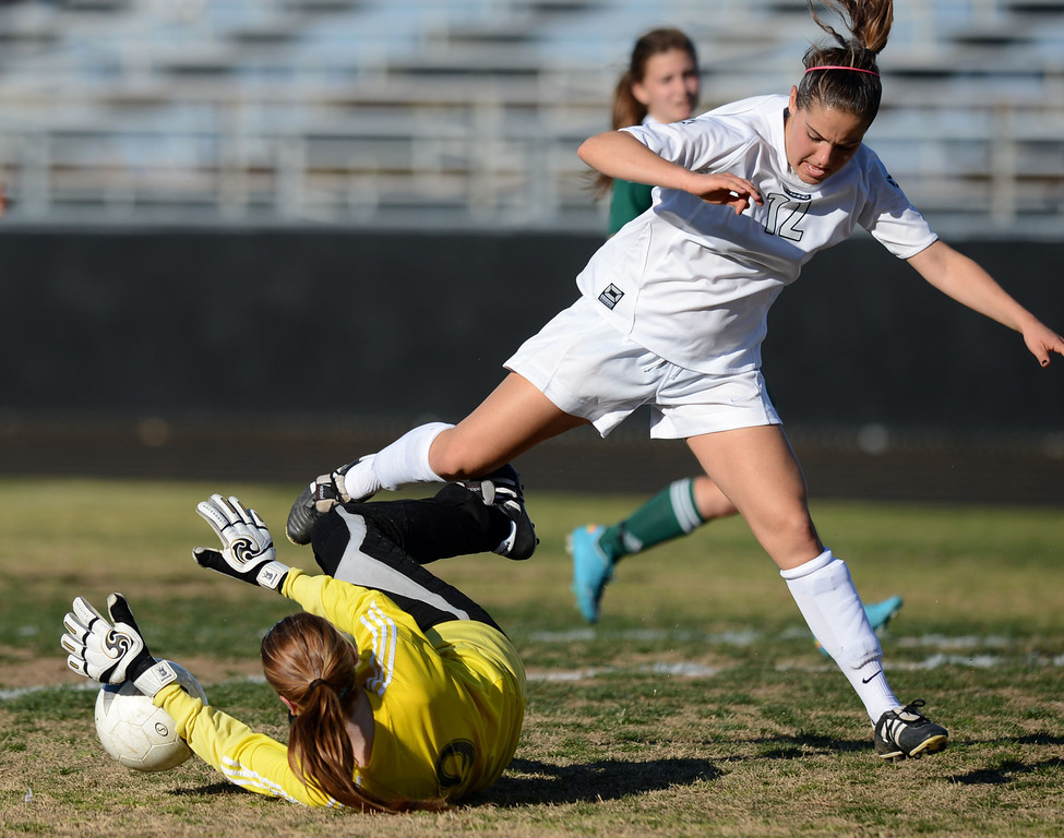 . Canyon keeper Meghan Kennedy (9) makes another diving stop on the ball under Peninsula\'s Michelle Duarte (12) in a CIF SS Division II first round soccer game Thursday in Rolling Hills Estates. After Peninsula seemingly dominated most of the game, Canyon scored a goal in the final two minutes to win 1-0. 20130214 Photo by Steve McCrank / Staff Photographer