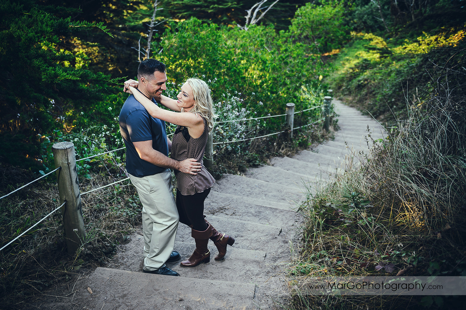 woman in brown tunic holding hands on neck of man in navy blue shirt on the wooden stairs during engagement session at San Francisco Lands End