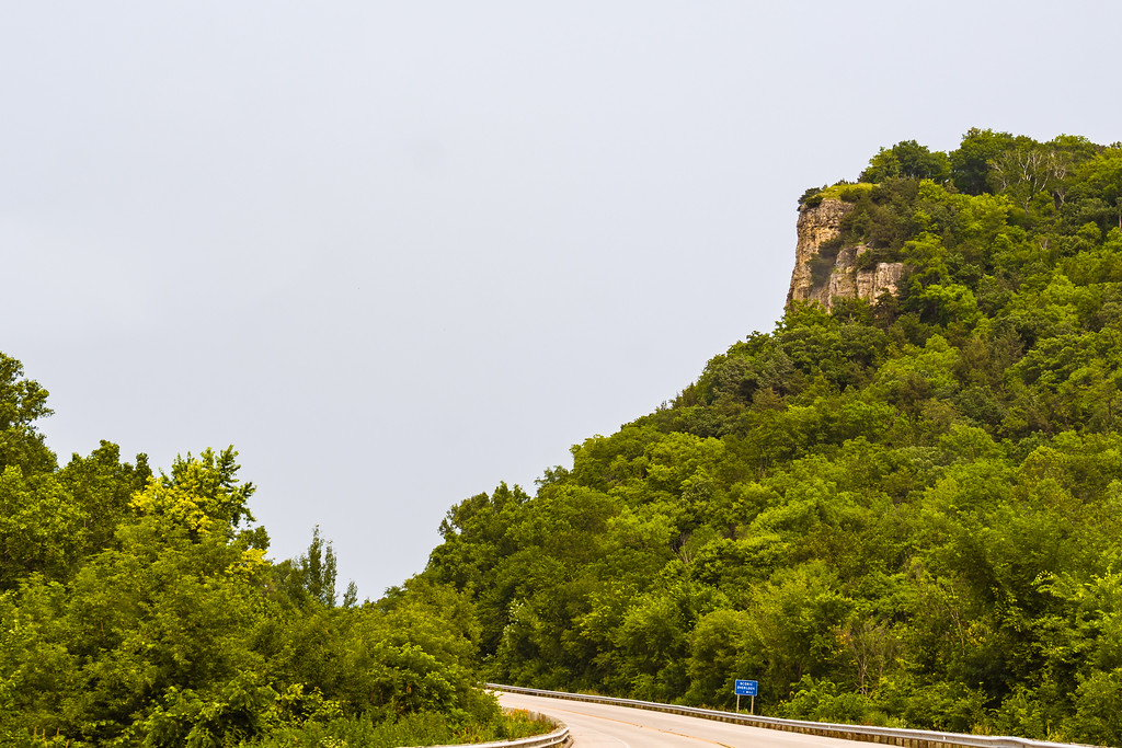 A highway curves around a tree-covered bluff with a rock outcropping on top