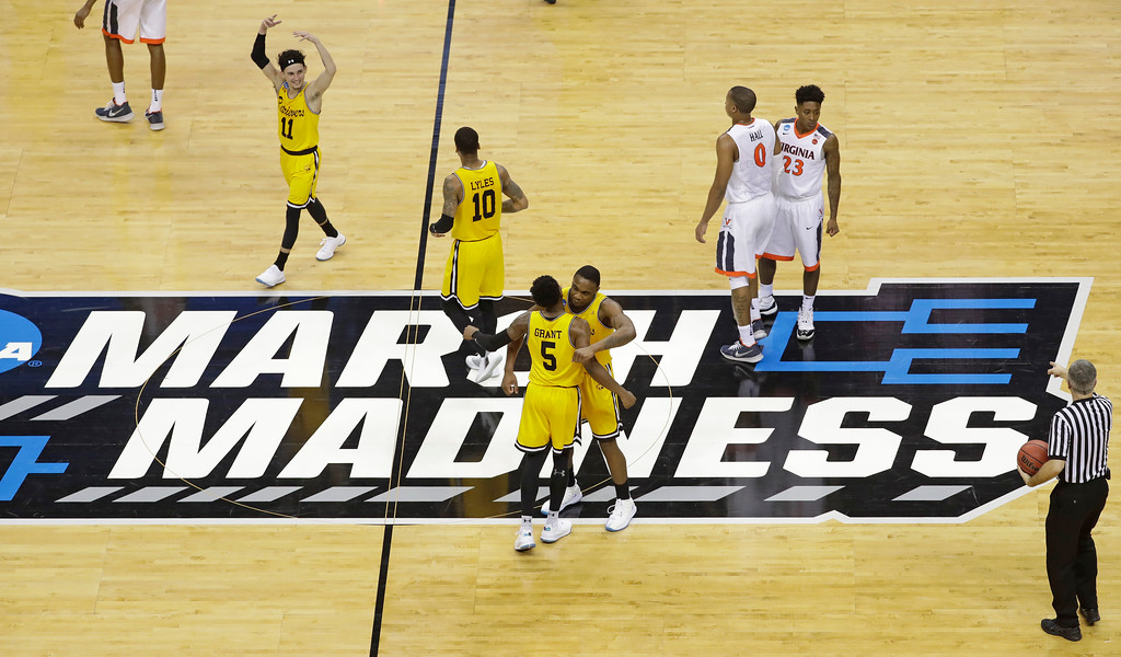 . UMBC players celebrate their 74-54 win over Virginia in a first-round game in the NCAA men\'s college basketball tournament in Charlotte, N.C., Friday, March 16, 2018. (AP Photo/Chuck Burton)