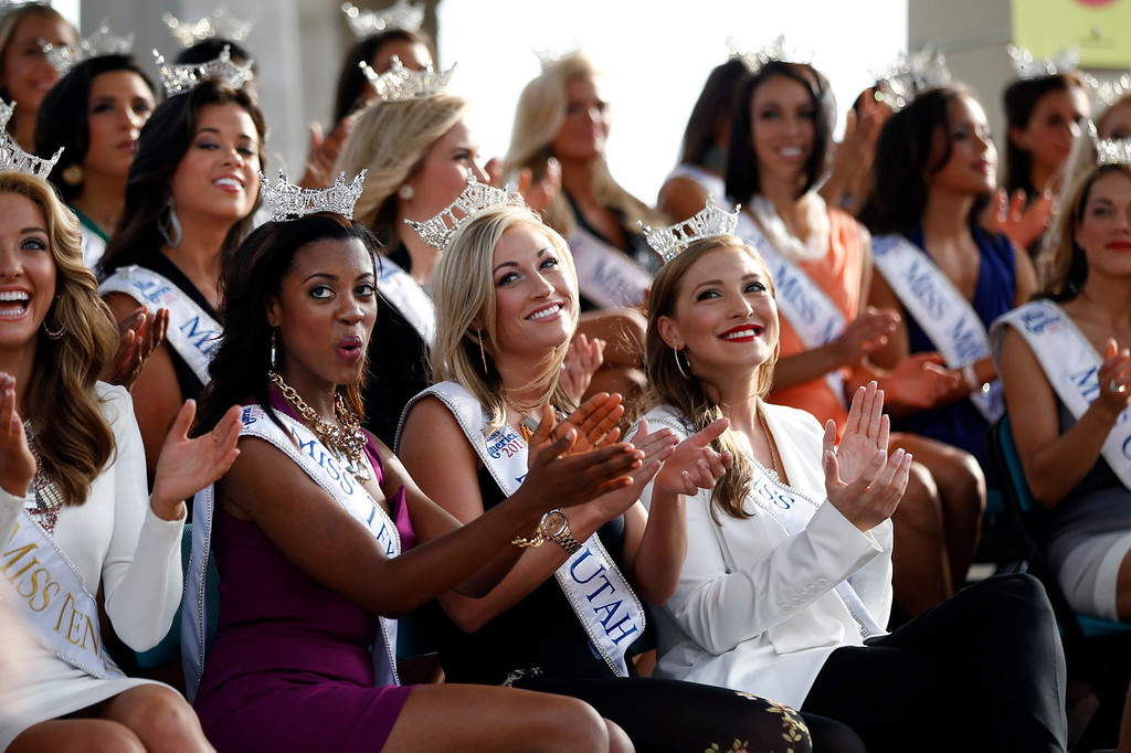 . Miss Tennessee Shelby Thompson, front  left, Miss Texas Ivana Hall, second front left, Miss Utah Ciera Pekarcik, third front left, and Miss Vermont Jeanelle Achee, fourth front left, applaud with other Miss America contestants during introductions after arriving in Atlantic City, N.J. on Tuesday, Sept. 3, 2013. The Miss America pageant is back in the city where it began, six years after spurning the city for Las Vegas. The pageant held a welcoming ceremony Tuesday for the 53 contestants, one from each state plus the District of Columbia, Puerto Rico and the U.S. Virgin n Islands. The contestants filed out of Boardwalk Hall, where the competition will begin next week and culminate days later, and walked across the Boardwalk to a stage. (AP Photo/Mel Evans)