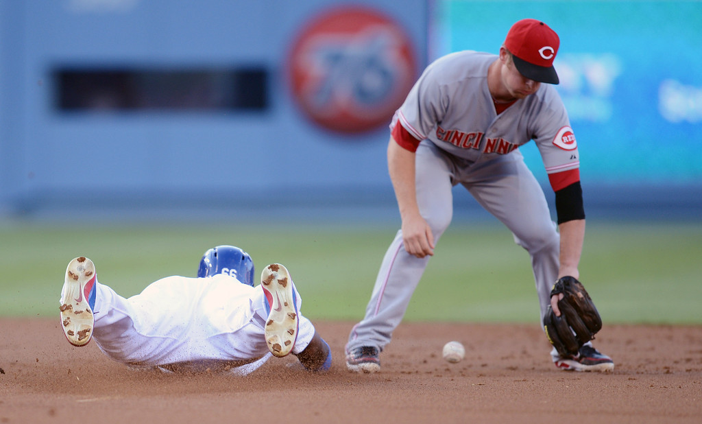 . The Dodgers Yasiel Puig slides in to second base as the Reds\' Zack Cozart #2 attempts to handle the throw during their game at Dodger Stadium in Los Angeles Saturday, July 27, 2013. (Hans Gutknecht/Los Angeles Daily News)