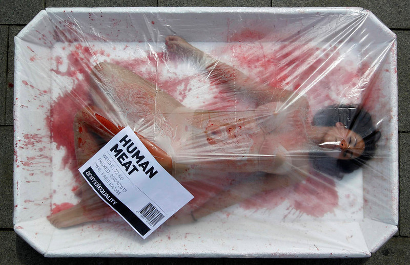 ". An animal rights activist protests against meat consumption through a performance to promote vegetarianism during ""Day Without Meat\"" in central Barcelona March 20, 2013. REUTERS/Albert Gea"