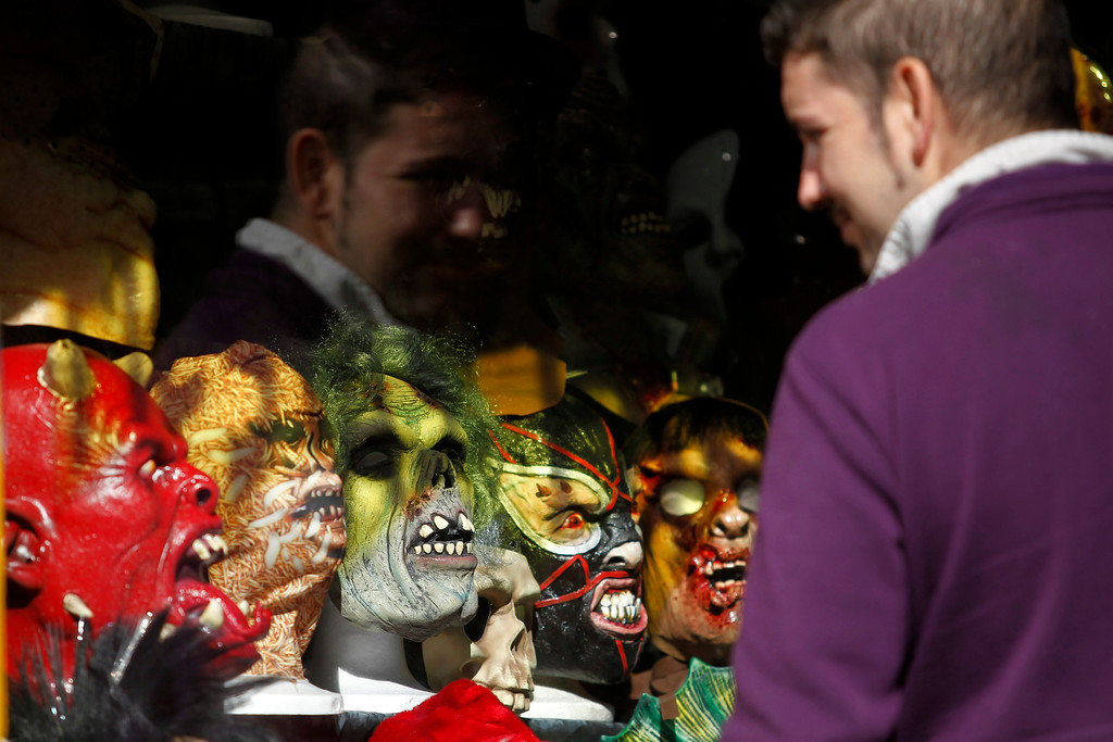 . A man looks at  horror masks displayed in a shop window in Madrid, Thursday, Oct. 31, 2013 before Halloween  celebrations. Pumpkins are traditionally bought and decorative faces carved out of them before masked costume parties at night to mark Halloween which occurs annually around the world on October 31. (AP Photo/Francisco Seco)