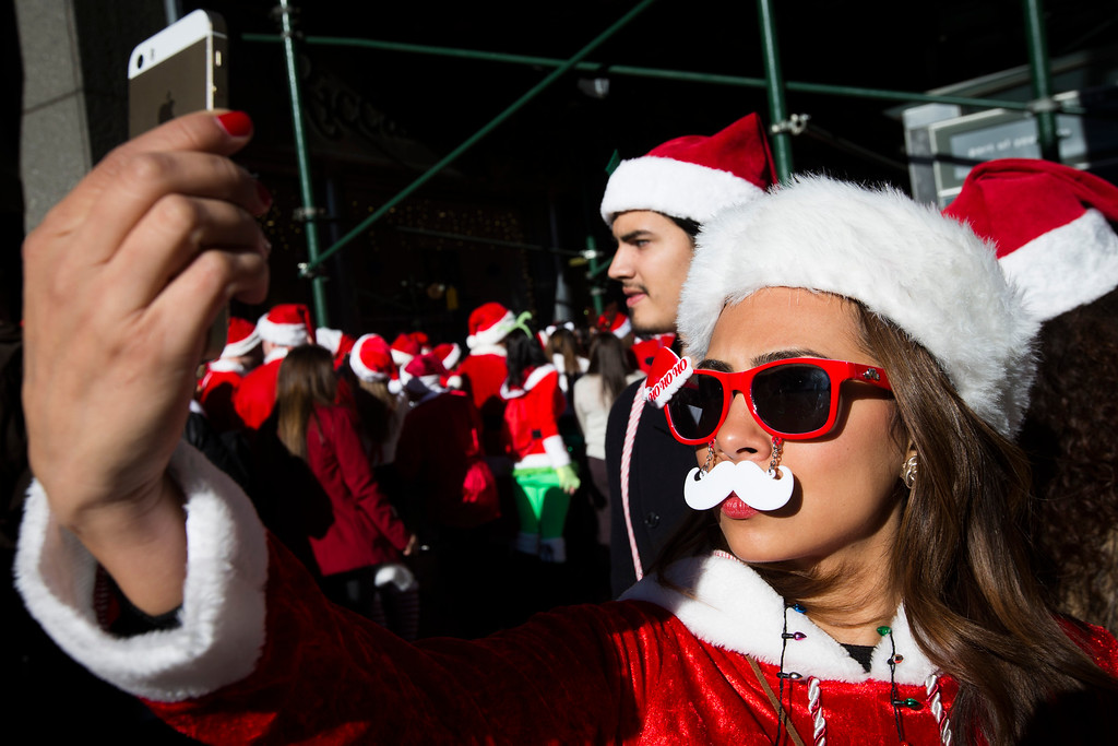 . A reveler dressed in a holiday theme costume takes a selfie during SantaCon, Saturday, Dec. 13, 2014, in New York.  SantaCon organizers retained lawyer Norman Siegel  last week as part of an effort to tame the excesses of the daylong party.  Siegel said the government cannot ban SantaCon. But he said the government can reasonably regulate the event. (AP Photo/John Minchillo)