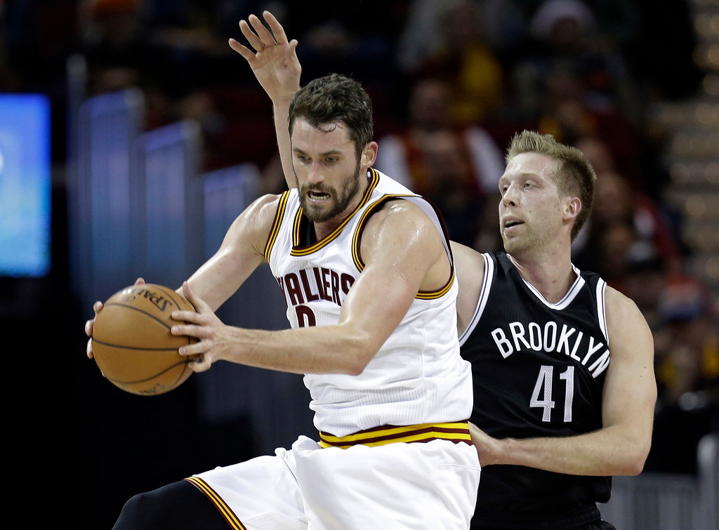 . Cleveland Cavaliers\' Kevin Love (0) grabs a pass against Brooklyn Nets\' Justin Hamilton (41) in the first half of an NBA basketball game, Friday, Dec. 23, 2016, in Cleveland. (AP Photo/Tony Dejak)