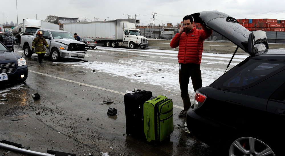 . Marc Milam of Rochester Hills, Mich. makes a phone call as authorities search a section of multi-vehicle accident on Interstate 75 is shown in Detroit, Thursday, Jan. 31, 2013. Snow squalls and slippery roads led to a series of accidents that left at least three people dead and 20 injured on a mile-long stretch of southbound I-75. More than two dozen vehicles, including tractor-trailers, were involved in the pileups.  (AP Photo/The Detroit News, David Coates)