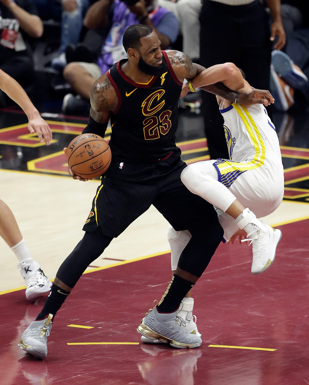 . Cleveland Cavaliers forward LeBron James (23) gets tied up with Golden State Warriors guard Stephen Curry (30) in the first half of Game 3 of basketball\'s NBA Finals, Wednesday, June 6, 2018, in Cleveland. (AP Photo/Tony Dejak)