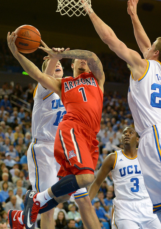 . Arizona\'s Gabe York is fouled by UCLA\'s David Wear while driving to the hoop, Thursday, January 9, 2014, at Pauley Pavilion. (Photo by Michael Owen Baker/L.A. Daily News)