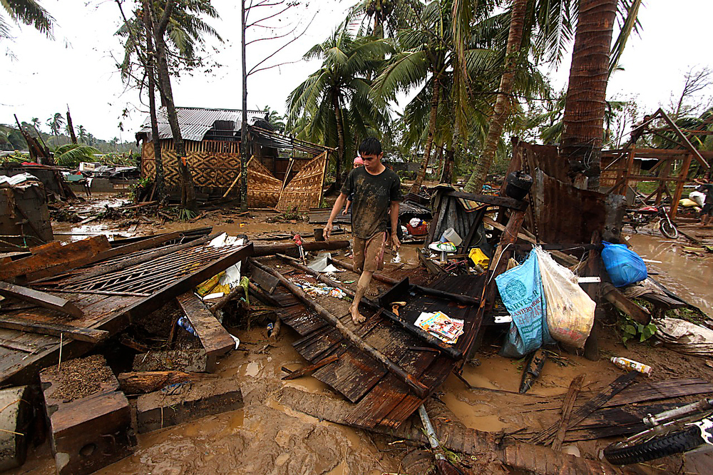 Description of . Residents walk amongst their destroyed houses after Typhoon Bopha hit Compostela town, Compostela Valley province, in southern island of Mindanao on December 4, 2012.  Typhoon Bopha killed 43 people in one hard-hit Philippine town December 4, local television station ABS-CBN reported from the scene. KARLOS MANLUPIG/AFP/Getty Images