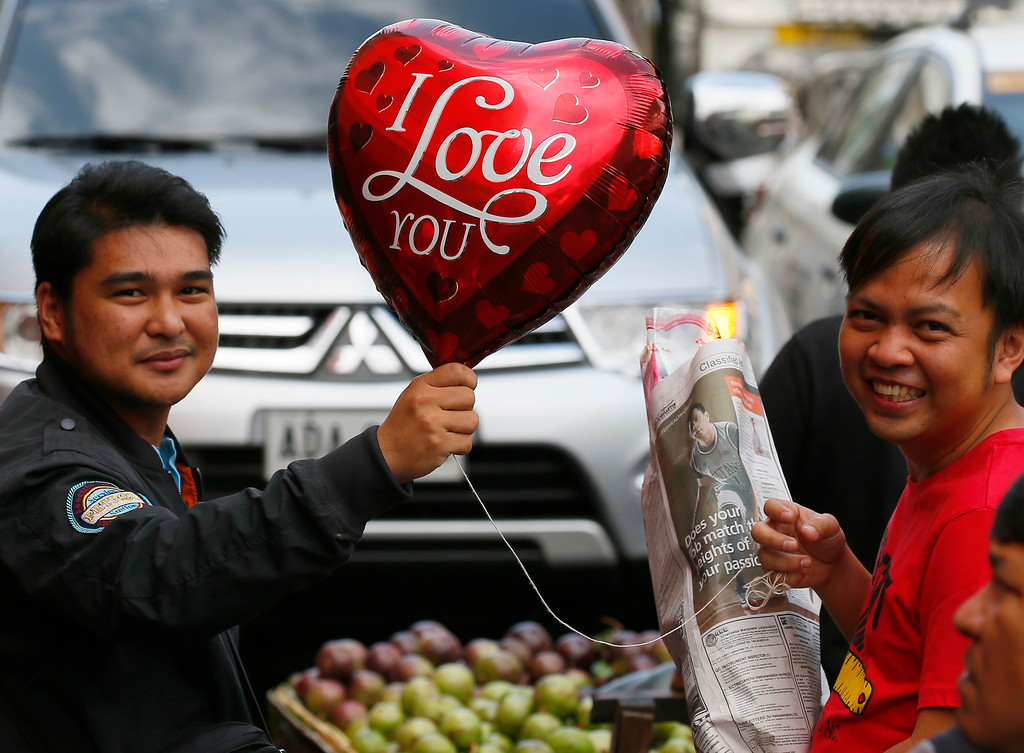 . A man holds a balloon for a friend as they buy flowers for their loved ones in celebration of Valentine\'s Day, Tuesday, Feb. 14, 2017, in Manila, Philippines. Valentine\'s Day, associated with love and romance, is expressed with flowers, chocolates, balloons and dinner dates. (AP Photo/Bullit Marquez)