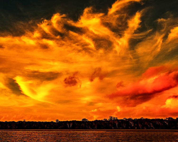 Orange colored stratocumulus cloud, sunset seascape.