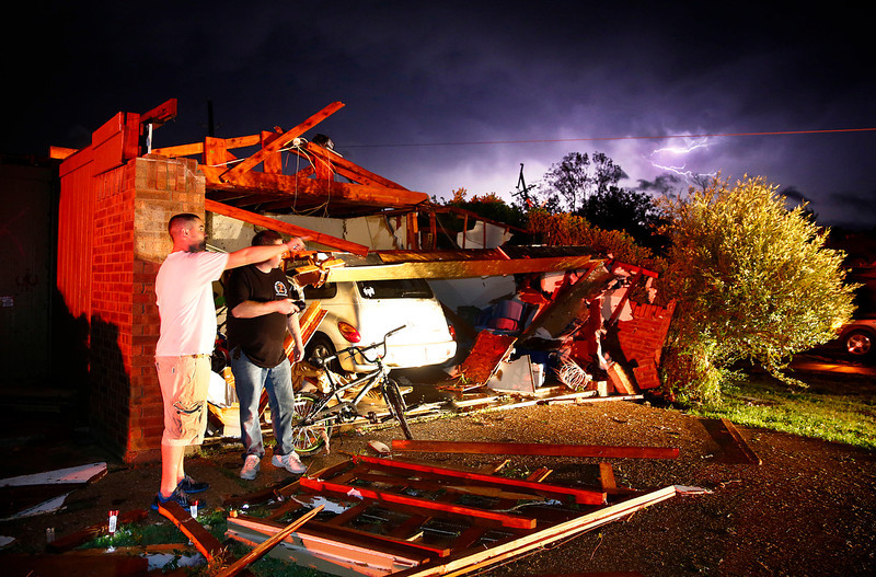 . Derrek Grisham, left, points out neighborhood damage to storm chaser Travis Schafer after a tornado damaged his mother\'s house on Hyde Park Lane at Country Club Rd. in Cleburne, Texas,Wednesday night, May 15, 2013. Cleburne Mayor Scott Cain early Thursday declared a local disaster as schools canceled classes amid the destruction. (AP Photo/The Dallas Morning News, Tom Fox)