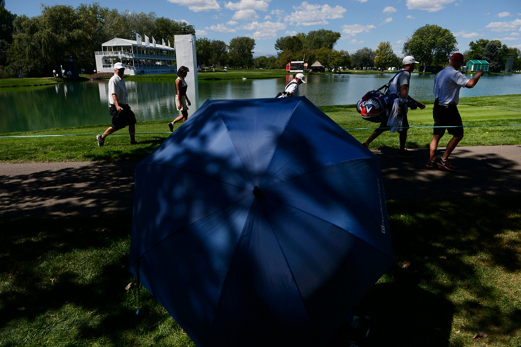 . CHERRY HILLS VILLAGE, CO. - SEPTEMBER 03:  A golf fan stays cool underneath an umbrella along the 18th fairway during the FedExCup BMW Championship Pro-Am at the Cherry Hills Country Club Wednesday, September 03, 2014. (Photo By Andy Cross / The Denver Post)