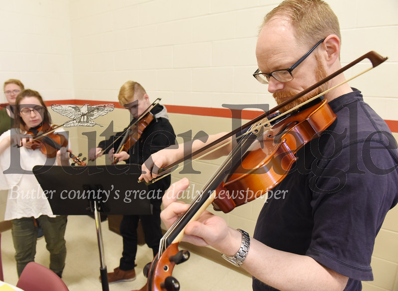 Harold Aughton/Butler Eagle: Ethan Eberle of Butler plays the violin with his wife, Vanessa, and son, Victor, 15, during the Salvation Army's Christmas Eve meal, Tuesday, December 24, 2019.