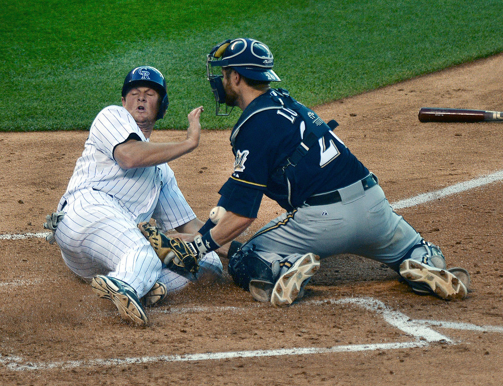 . DENVER, CO - JUNE 20: Colorado baserunner DJ LeMahieu crossed the plate safely in the second inning after Milwaukee catcher Jonathan Lucroy lost his grip on the ball. The Colorado Rockies hosted the Milwaukee Brewers at Coors Field Friday night, June 20, 2014. Photo by Karl Gehring/The Denver Post
