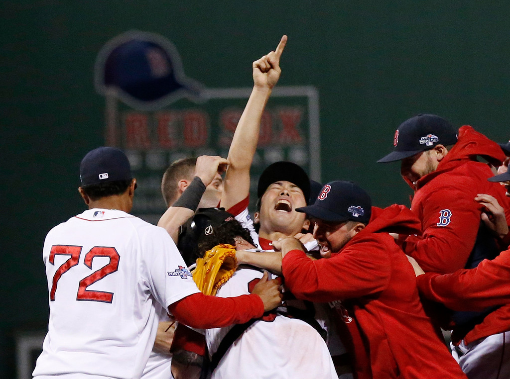 . Boston Red Sox relief pitcher Koji Uehara, center, celebrates with teammates after the Red Sox 5-2 beat the Detroit Tigers in Game 6 of the American League baseball championship series on Saturday, Oct. 19, 2013, in Boston. The Red Sox advance to the World Series. (AP Photo/Tim Donnelly)
