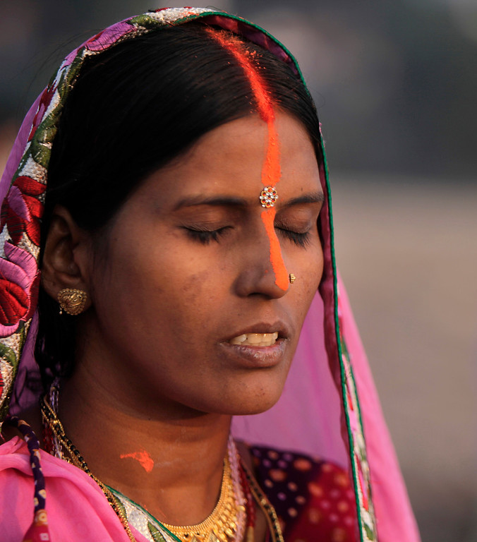 . A Hindu devotee offers prayers to the Sun God in the Tawi River during Chhath Puja festival in Jammu, India, Friday, Nov. 8, 2013.  (AP Photo/Channi Anand)