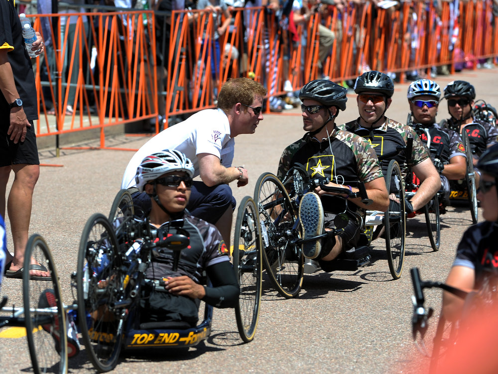 . HRH Prince Harry talks to competitors in the 10K Recumbent race before the start of the race.  The fourth annual Warrior Games cycling event took started and finished at Falcon Stadium on the grounds of the Air Force Academy in Colorado Springs, CO on May 12, 2013.  HRH Prince Harry was on hand to start the race as well as to hand out medals at the finish line.   A total of 260 wounded, ill and injured service members and veterans came to compete in the week long games.  Members of the Army, Marine Corps, Navy/Coast Guard/Air Force. Special Operations and the British Armed Forces all took part in the competition.  Other events included in the Warrior Games are shooting, sitting volleyball, track & field and wheelchair basketball.  (Photo by Helen H. Richardson/The Denver Post)