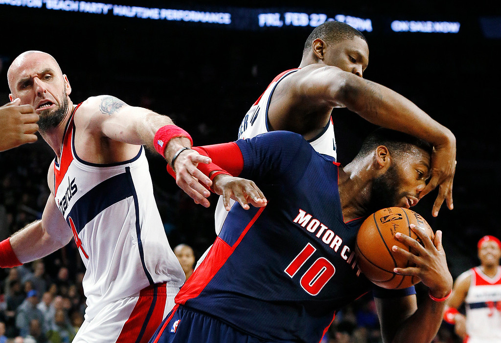 . Detroit Pistons\' Greg Monroe (10) pulls down a rebound in front of Washington Wizards\' Marcin Gortat, left, as he fouled by Washington Wizards\' Kevin Seraphin in the second half of an NBA basketball game, Sunday, Feb. 22, 2015, in Auburn Hills, Mich. (AP Photo/Paul Sancya)
