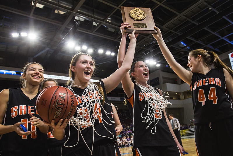 BANGOR, MAINE -- 02/25/2017 -- Shead High Schools girls basketball senior captains Katelyn Mitchell (left) and Holly Preston (center) and teammate Cassidy Wilder (right) hold their team's championship plaque into the air for cheering fans, surrounded by their other teammates, following their class D girls final basketball game against Southern Aroostook at the Cross Insurance Center in Bangor on Saturday morning. Micky Bedell | BDN