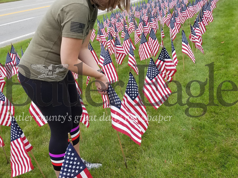 Megan Klingensmith place one flag in a memorial of 660 that represents the total number of veterans who die by suicide each month.