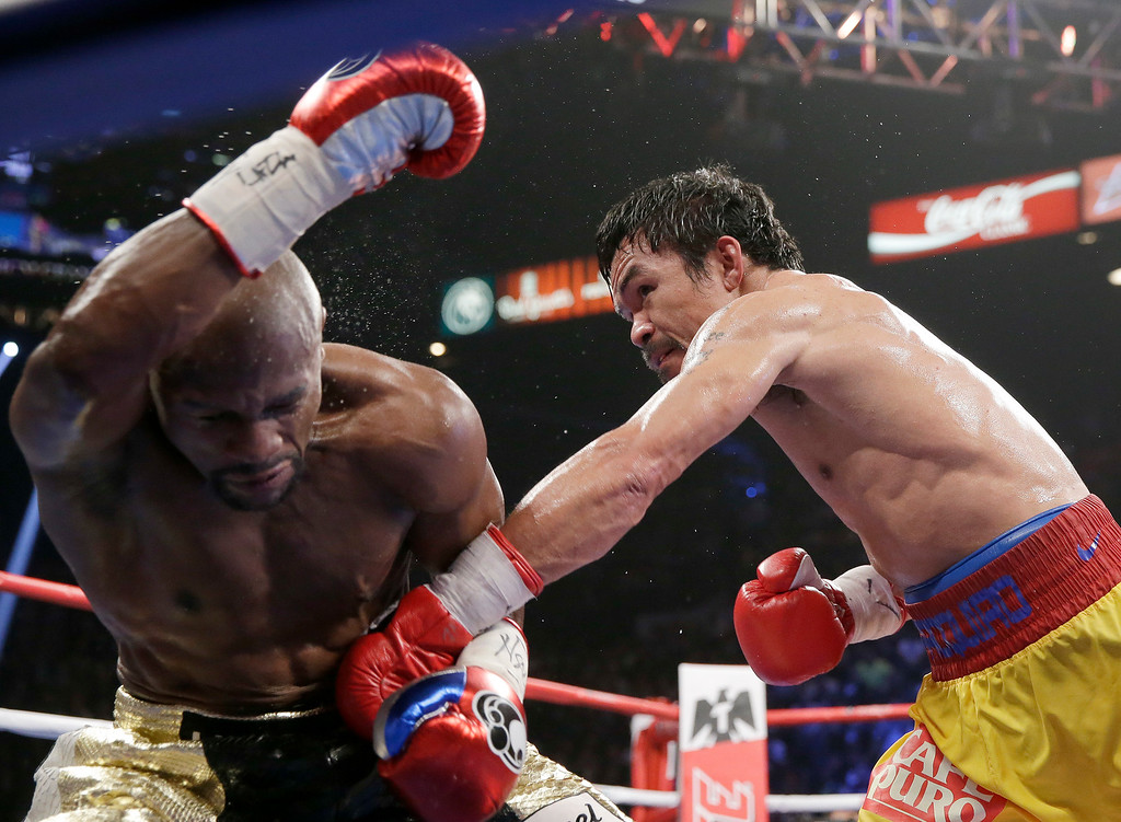 . Manny Pacquiao, from the Philippines, right, punches Floyd Mayweather Jr., during their welterweight title fight on Saturday, May 2, 2015 in Las Vegas. (AP Photo/Isaac Brekken)