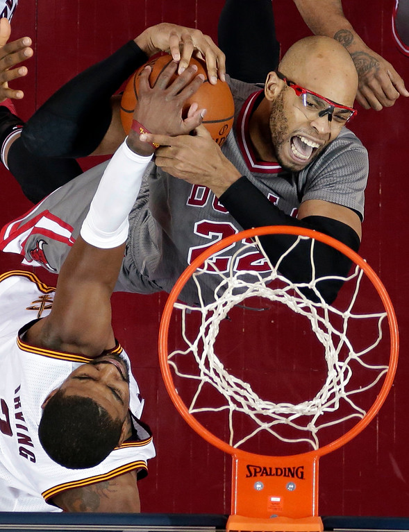 . Chicago Bulls� Taj Gibson, right, is stopped by Cleveland Cavaliers\' Kyrie Irving (2) on a drive to the basket during the first half of an NBA basketball game Saturday, Jan. 23, 2016, in Cleveland. (AP Photo/Tony Dejak)