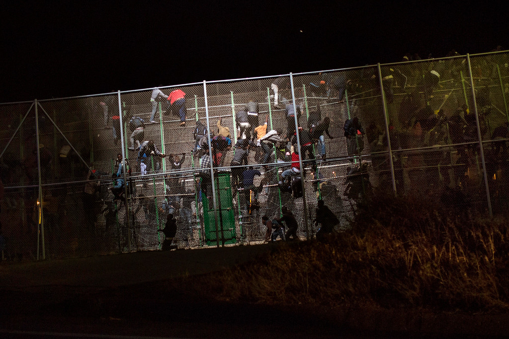 . Sub-Saharan migrants scale a metallic fence that divides Morocco and the Spanish enclave of Melilla, early in the morning on Wednesday, May 28,  2014. Several hundred African migrants charged the barbed-wire border fence in Spain�s North African enclave of Melilla with many managing to get across while dozens of others were beaten back by Moroccan and Spanish police. During the pre-dawn border storming, cries of pain and noises of people being hit could be heard as police from both sides tried to prevent dozens of the sub-Saharan migrants from entering the city from Morocco. (AP Photo/Santi Palacios, File)