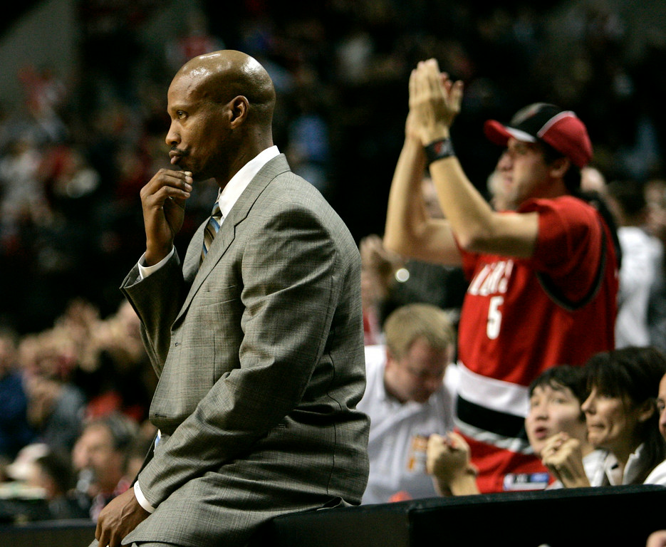 . New Orleans Hornets  head coach Byron Scott sits on the scorers bench while a Blazers fan cheers in the background late in the second half or their NBA basketball game against the Portland Trail Blazers in Portland, Ore., Friday, Nov. 10, 2006.  The Hornets lost to the Blazers 92-91.(AP Photo/Don Ryan)