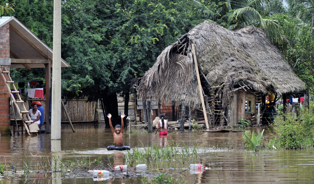 . A boy plays in his house back yard flooded by the overflowing of the Beni river and heavy rains hitting the country, in Reyes, department of Beni, northeast Bolivia, on February 2, 2014. (AIZAR RALDES/AFP/Getty Images)