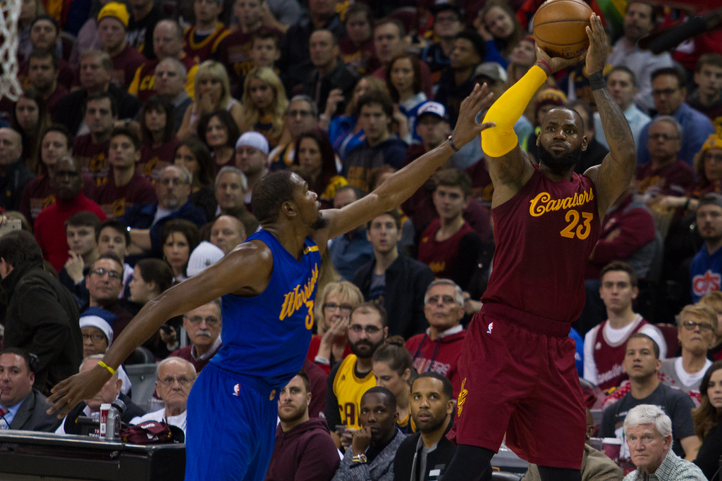 . LeBron James (23) of the Cleveland Cavaliers takes a three pointer over the Warriors\' Kevin Durant (35) during an NBA game at the Quicken Loans Arena on Christmas day.  The Cavs defeated the Warriors 109-108.  Michael Johnson - The News Herald