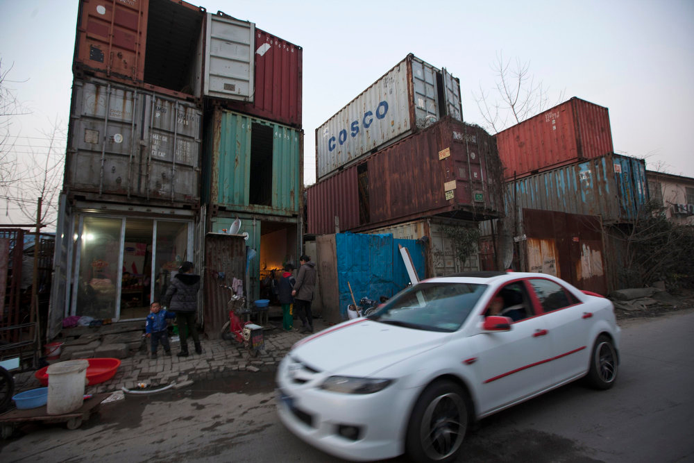 . People stand outside shipping containers serving as their accommodation, as a car passes through a street, in Shanghai March 4, 2013. The containers, which house different families, were set up by the landlord, who charges a rent of 500 yuan ($ 80) per month for each container. REUTERS/Aly Song